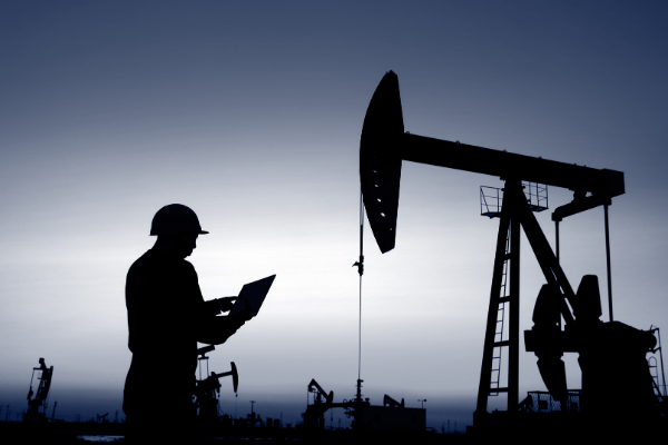 silhouette of a man using a laptop on an oil field